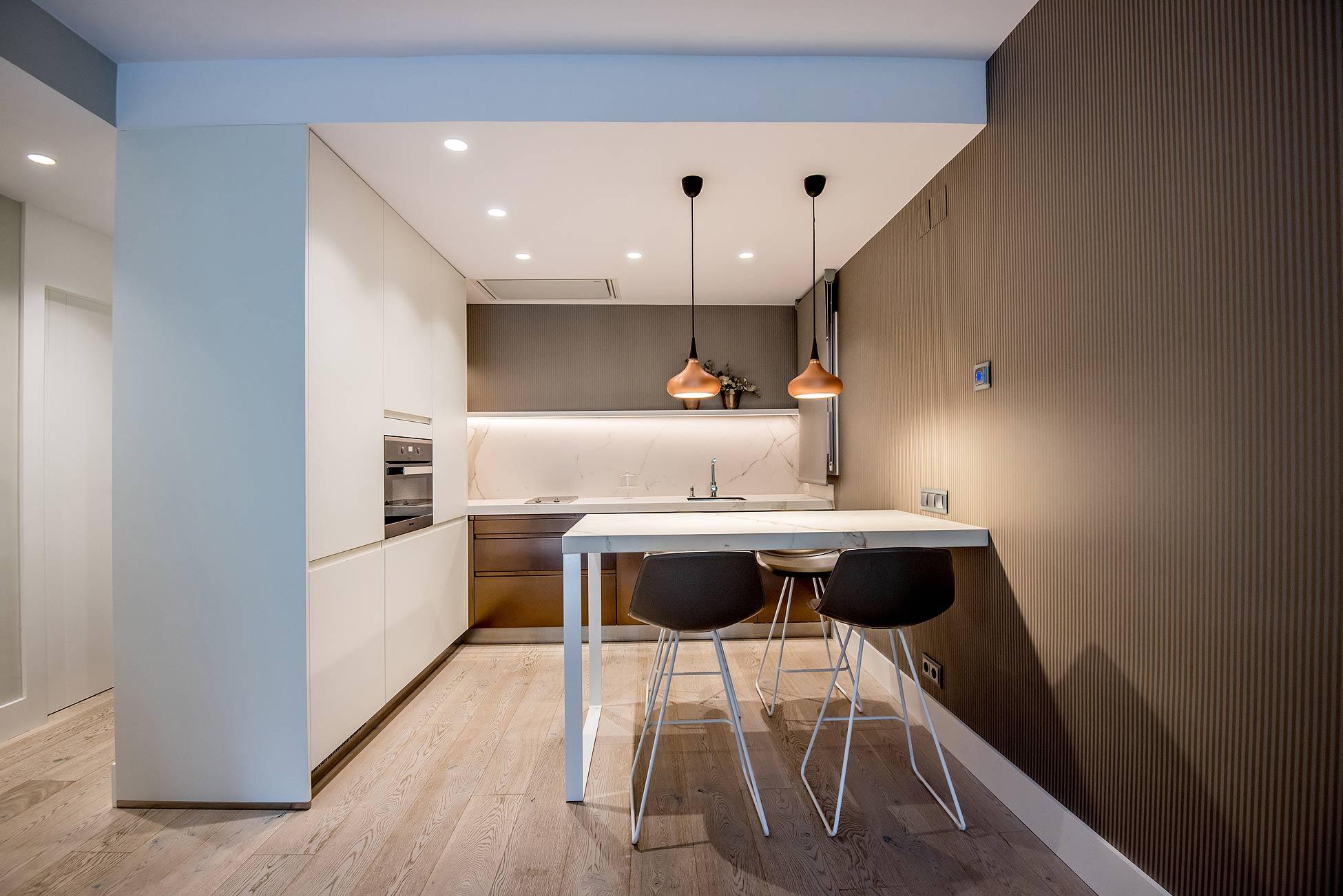 Cocina integrada en el salón comedor con toques en bronce